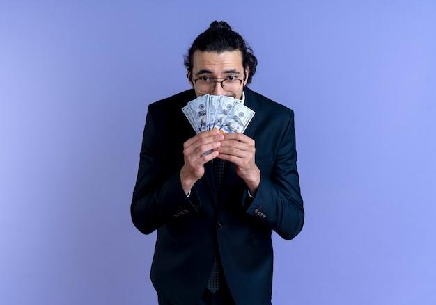 Homem de negócios de terno preto e óculos segurando dinheiro parecendo surpreso e surpreso em pé sobre a parede azul