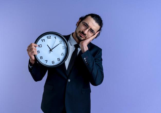 Homem de negócios de terno preto e óculos segurando um relógio de parede, parecendo cansado e sobrecarregado, fazendo gesto para dormir em pé sobre a parede azul