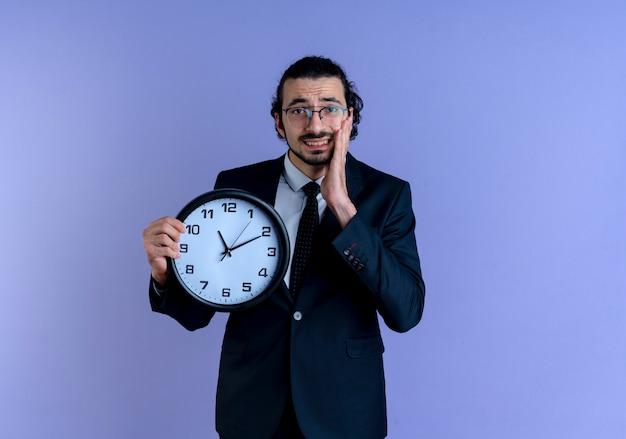 Homem de negócios de terno preto e óculos segurando um relógio de parede parecendo confuso em pé sobre a parede azul