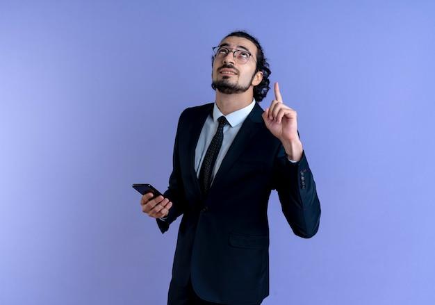 Homem de negócios de terno preto e óculos segurando um smartphone apontando com o dedo indicador para cima, parecendo confiante em pé sobre a parede azul
