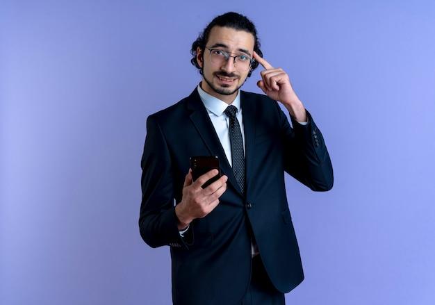 Homem de negócios de terno preto e óculos segurando um smartphone apontando com o dedo sua têmpora, parecendo confuso em pé sobre a parede azul