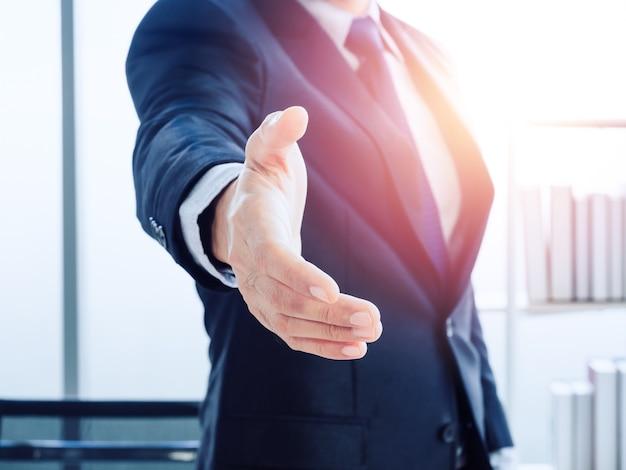 Homem de negócios de terno segurando a mão esperando um aperto de mão