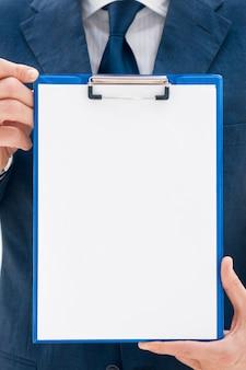 Homem de negócios de terno segurando uma prancheta em branco pronta para seu texto ou imagem