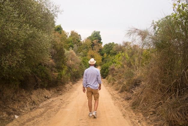 Homem de negócios de trás em uma longa estrada rural