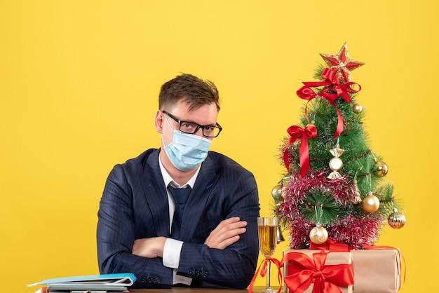 Homem de negócios de vista frontal cruzando as mãos, sentado à mesa perto da árvore de natal e presentes em fundo amarelo