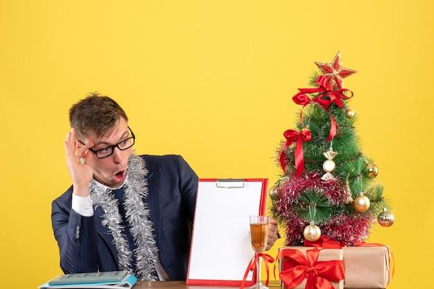 Homem de negócios de vista frontal verificando o papel sentado à mesa perto da árvore de natal e presentes em fundo amarelo