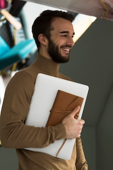Homem de negócios de vista lateral com laptop e agenda