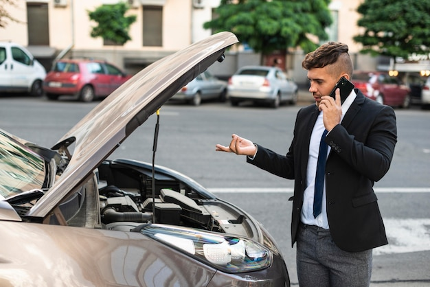 Homem de negócios de vista lateral falando com o serviço de carro