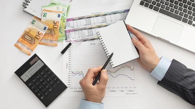 Homem de negócios de vista superior verificando os modos de finanças