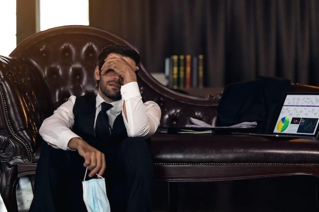 Homem de negócios deprimido com os olhos fechados de mãos dadas na cabeça e papel com gráficos no escritório