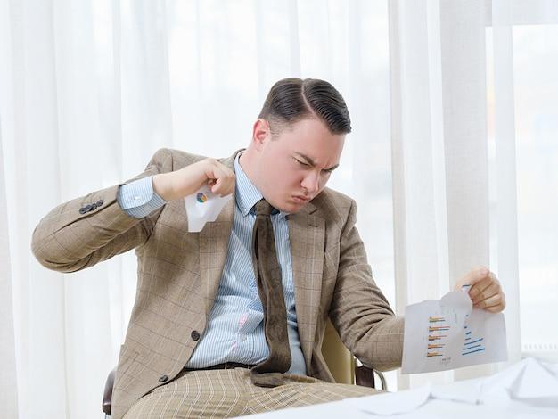 Homem de negócios desapontado com raiva rasgando documentos em pedaços.