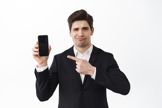 Homem de negócios desapontado e carrancudo apontando para a tela do telefone vazia, julgando uma promoção ruim, não gosto de site, oferta promocional esfarrapada, em pé sobre uma parede branca