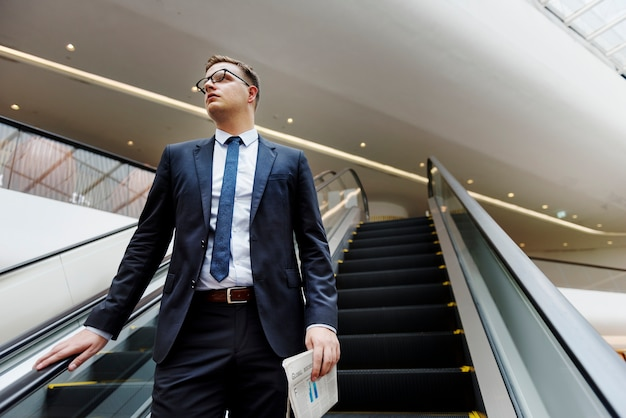 Homem de negócios, descendo o conceito de escada rolante