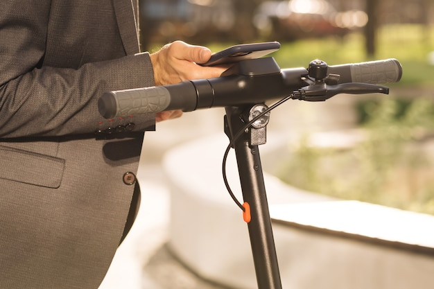 Homem de negócios desconhecido em um terno clássico aproxima-se de uma scooter elétrica e usa um aplicativo para celular