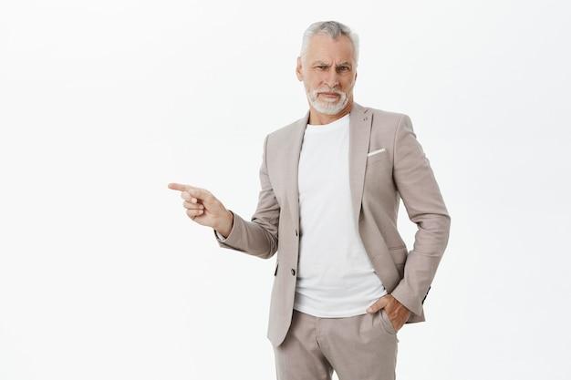 Homem de negócios descontente incomodado de terno apontando o dedo para a esquerda e fazendo careta de desapontamento