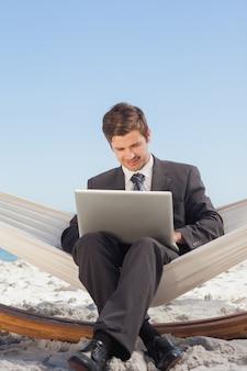 Homem de negócios digitando em seu laptop em uma rede e sorrindo
