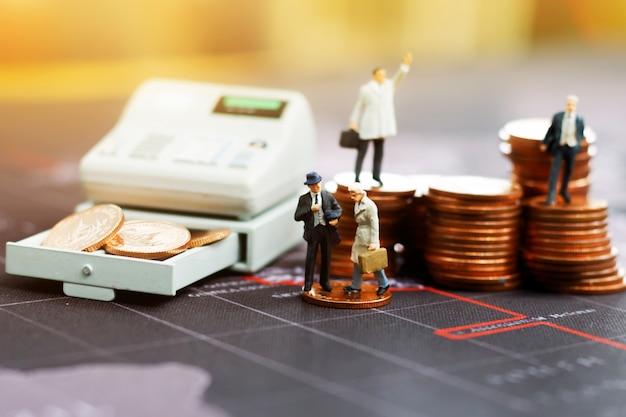 Homem de negócios diminuto com pilha de moedas.