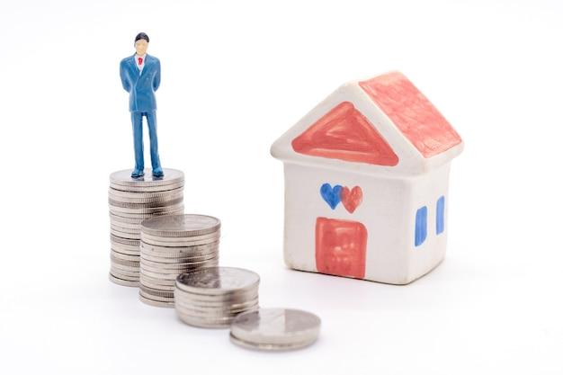 Homem de negócios diminuto que está em moedas e na casa atrás. conceito de poupança e empréstimo.