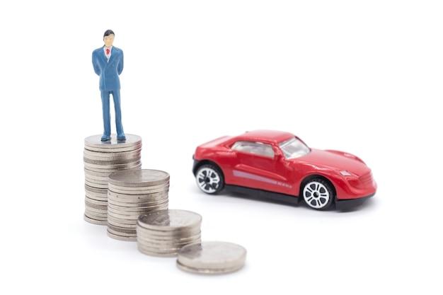 Homem de negócios diminuto que está em moedas e no carro atrás. conceito de poupança e empréstimo.