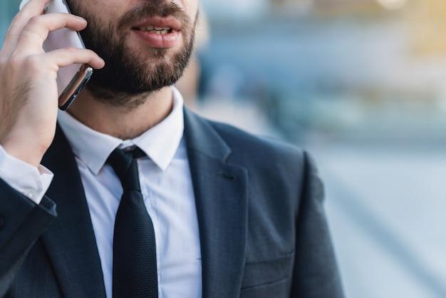 Homem de negócios do close-up que fala no smartphone contra o negócio que constrói fora.