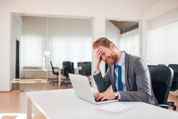 Homem de negócios do gengibre que ri ao usar o portátil no escritório.