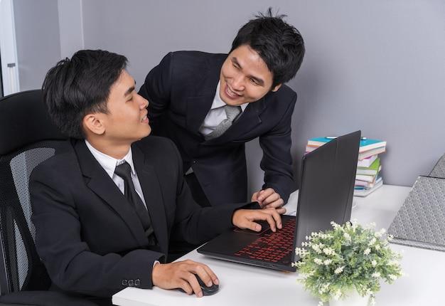 Homem de negócios dois rindo enquanto estiver usando o computador portátil