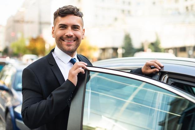 Homem de negócios e carro de vista frontal