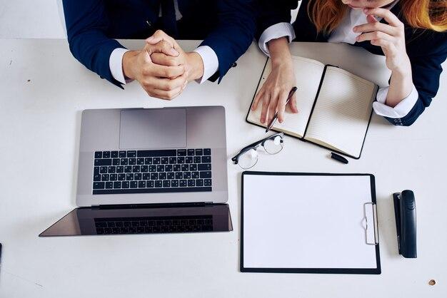 Homem de negócios e laptop de mulher e documentos em cima da mesa. foto de alta qualidade
