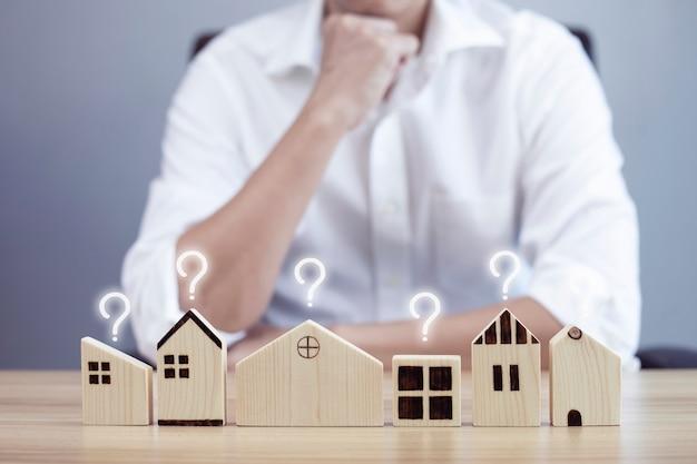 Homem de negócios e modelo de casa pequena com ponto de interrogação