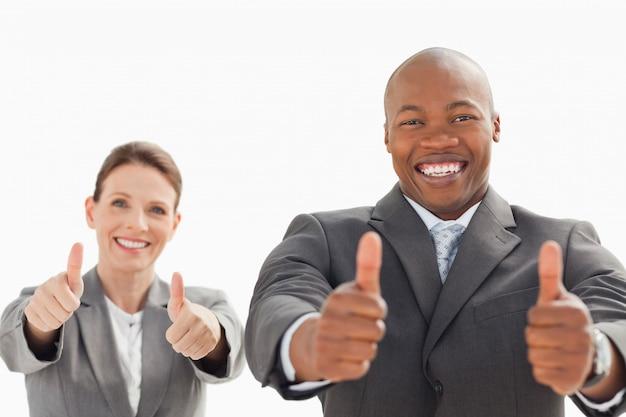 Homem de negócios e mulher com seus polegares para cima