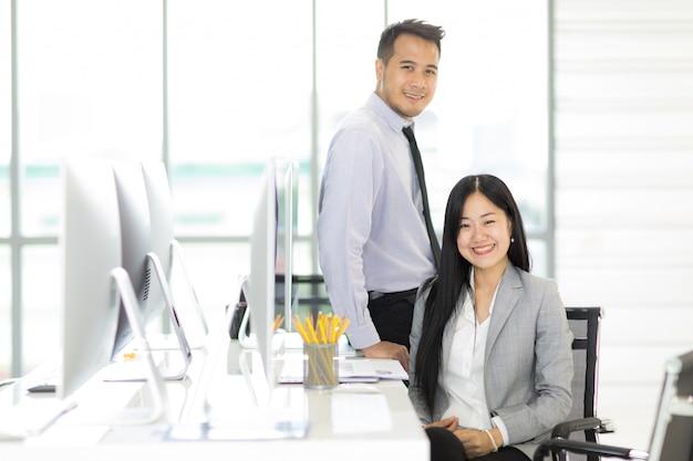 Homem de negócios e mulher de negócios de asain dois que relaxam junto no escritório.