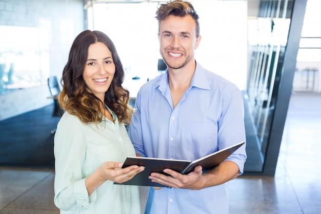 Homem de negócios e mulher de negócios interagindo segurando organizador no escritório