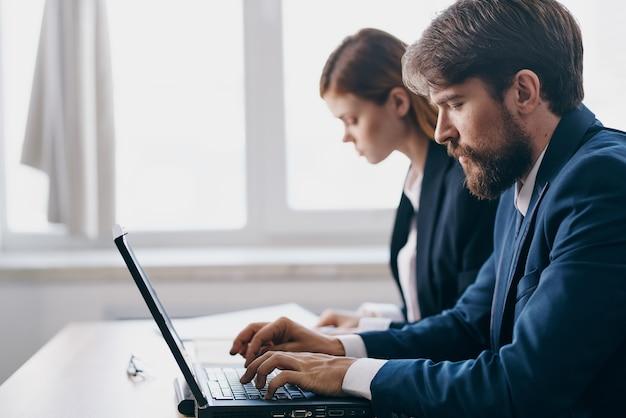 Homem de negócios e mulher no escritório na frente de tecnologias de rede de carreira de um laptop. foto de alta qualidade