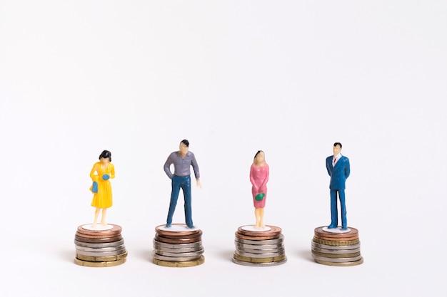 Homem de negócios e mulher sentada em pilhas iguais de moedas