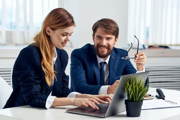 Homem de negócios e mulher sentados à mesa em frente à equipe de tecnologia do laptop