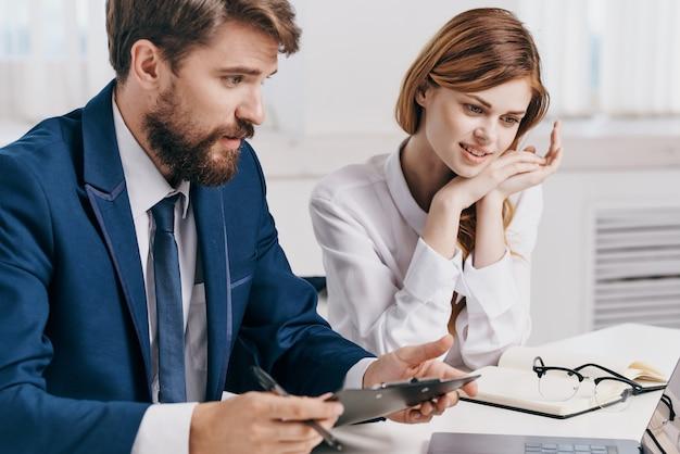 Homem de negócios e mulher sentados à mesa em frente à tecnologia de profissionais de laptop