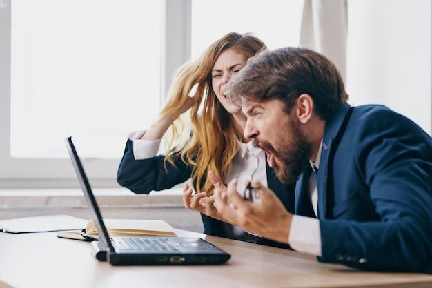 Homem de negócios e mulher sentados em frente a um laptop, profissionais do trabalho em equipe