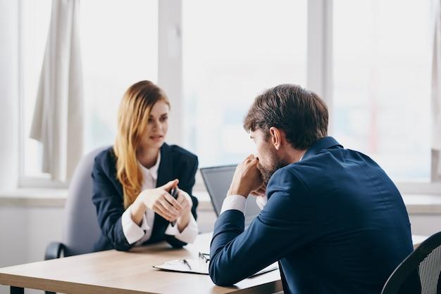 Homem de negócios e mulher sentados em frente a um laptop, trabalho em equipe, tecnologias de internet