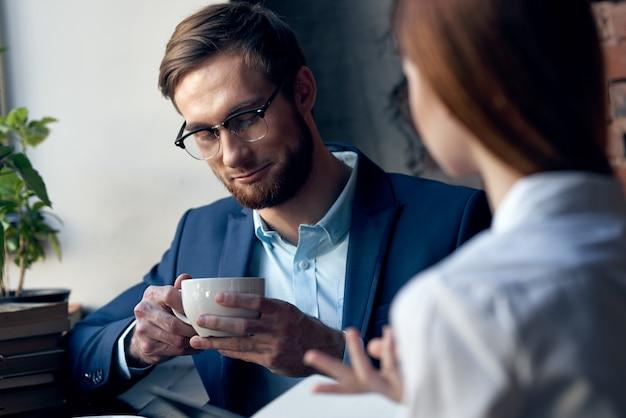 Homem de negócios e mulher sentados no café, socializando no café da manhã, estilo de vida