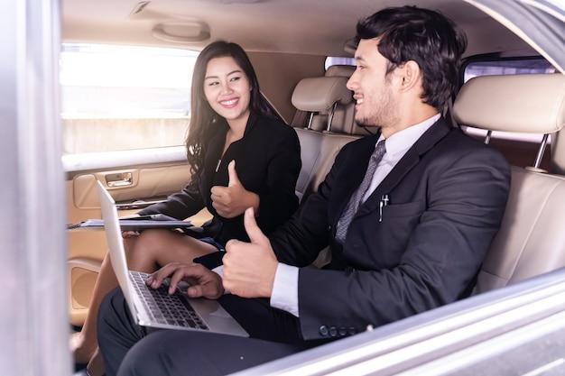 Homem de negócios e negócios mulher sentada e polegares para cima no carro, trabalhando no laptop.