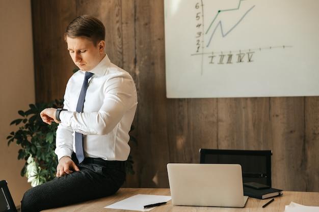 Homem de negócios e trabalhador de escritório se senta à mesa em seu escritório e observa as horas em seu relógio de pulso.