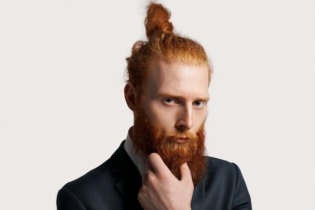 Homem de negócios eficaz e talentoso com cabelo ruivo com visão forte e segura a barba com as mãos