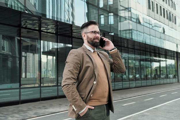 Homem de negócios elegante conversa no celular enquanto está ao ar livre na cidade