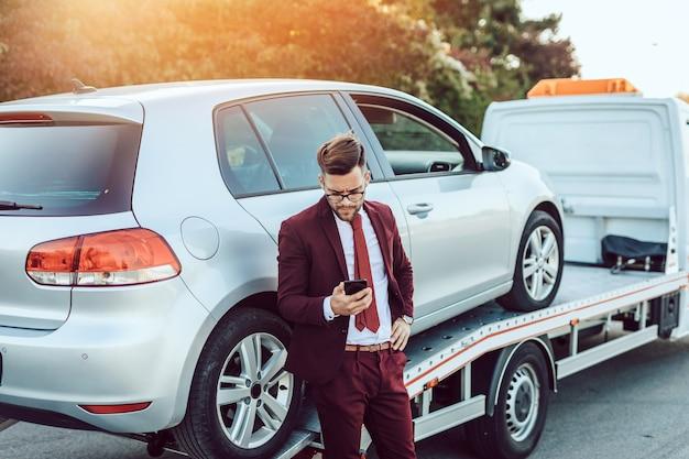 Homem de negócios elegante de meia-idade, chamando o serviço de reboque para obter ajuda na estrada. conceito de assistência na estrada.