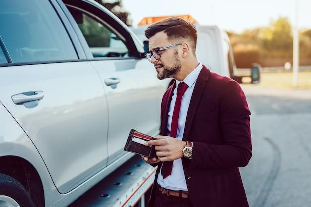 Homem de negócios elegante de meia-idade usando o serviço de reboque para socorrer o acidente de carro na estrada. conceito de assistência na estrada.