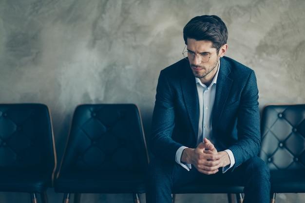 Homem de negócios elegante posando contra a parede cinza