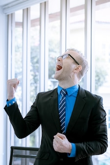 Homem de negócios em agir feliz e alegre para o sucesso no plano de marketing e vendas alvo