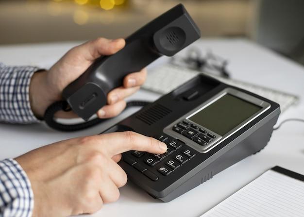 Homem de negócios em close discando número de telefone