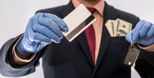 Homem de negócios em luvas médicas segurando um cartão de crédito e a chave do carro, com dinheiro no poket, epidemia covi19, segurança eberybody