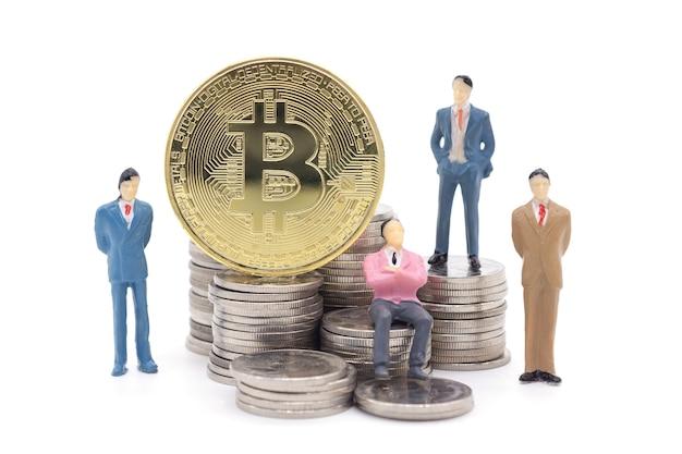 Homem de negócios em miniatura e bitcoin em fundo branco